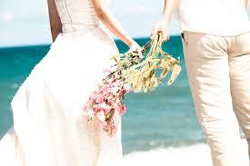 フリー素材   海辺の白い砂浜の花束を持ったカップルの写真。幸せそうな雰囲気が結婚にぴったり。